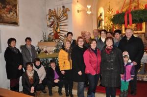 Die Patinnen und Paten der Krippenfiguren mit der neuen Weihnachtskrippe links im Hintergrund. (Foto: mb)