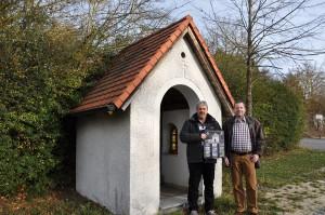 Klaus Söllner und Joachim Kliemke mit dem 2016er OGV-Kalender vor dem Köpfkircherl am Ortsausgang von Beratzhausen. Foto: Markus Bauer